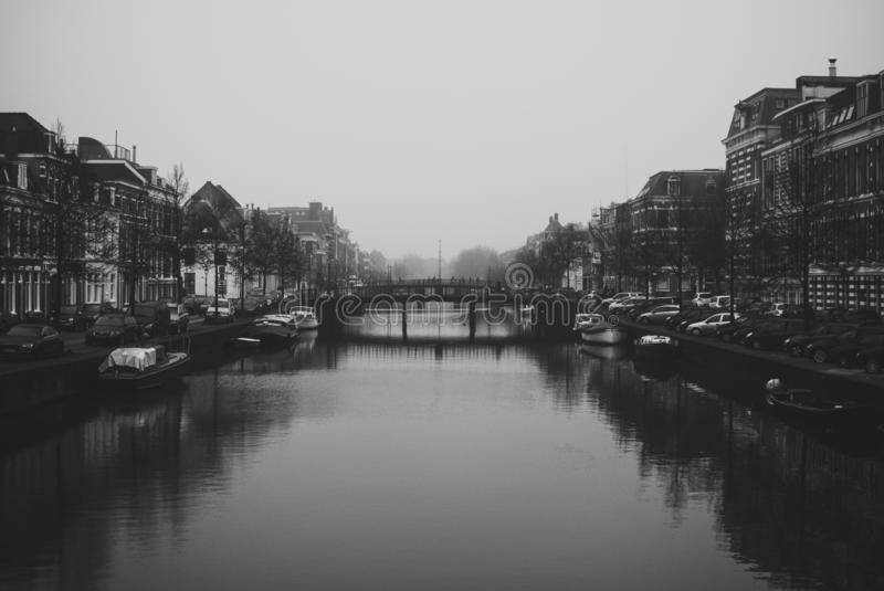 Charming cityscape of old Dutch town Haarlem. Stone bridge connecting two banks of the Spaarne river. Beautiful perspective. Misty and cloudy early spring stock photos