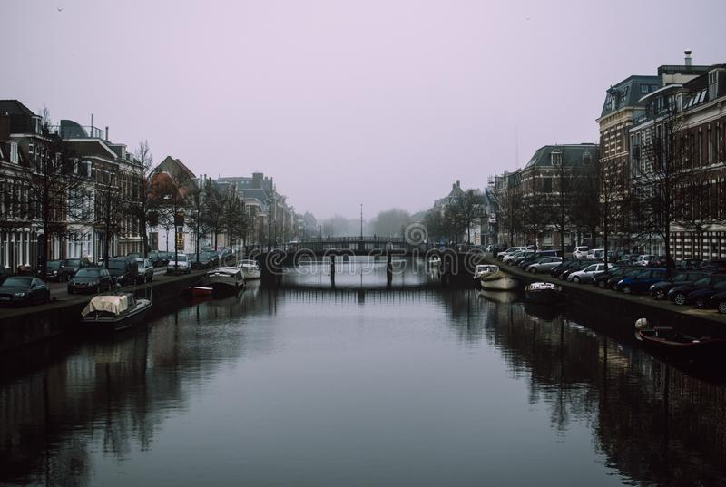 Charming cityscape of old Dutch town Haarlem. Stone bridge connecting two banks of the Spaarne river. Calm blue water and black shadows. Beautiful perspective stock photo