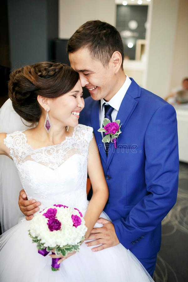 Charming couple bride and groom in the lobby laughing and genuinely smiling positive portrait. Sincere feelings, strong stock images