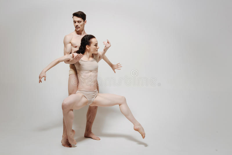 Charming creative couple performing isolated in white background. In close connection. Slim muscular unemotional dancers standing in the studio and dancing while royalty free stock photography