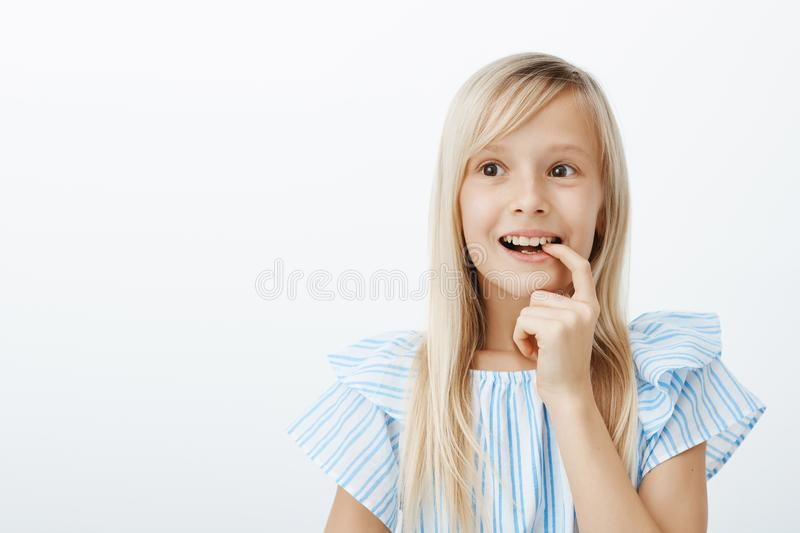 Charming creative young girl has great idea, deciding what to draw for mother birthday. Portrait of dreamy adorable royalty free stock photography