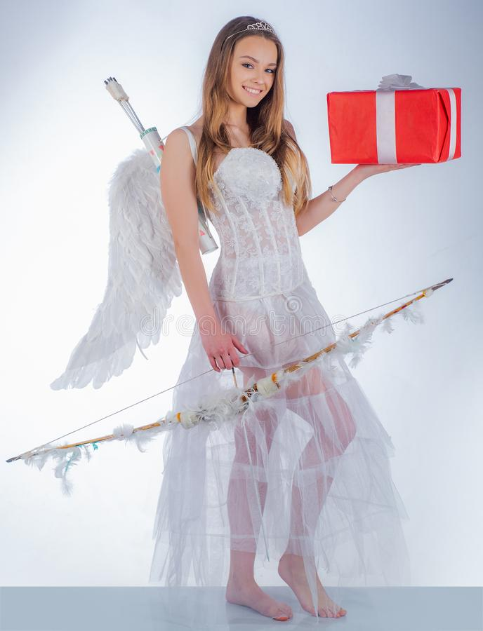 Charming curly woman in white dress and wings - angel cupid girl. arrow and wings. Angel girl with blonde hair. Real stock photography