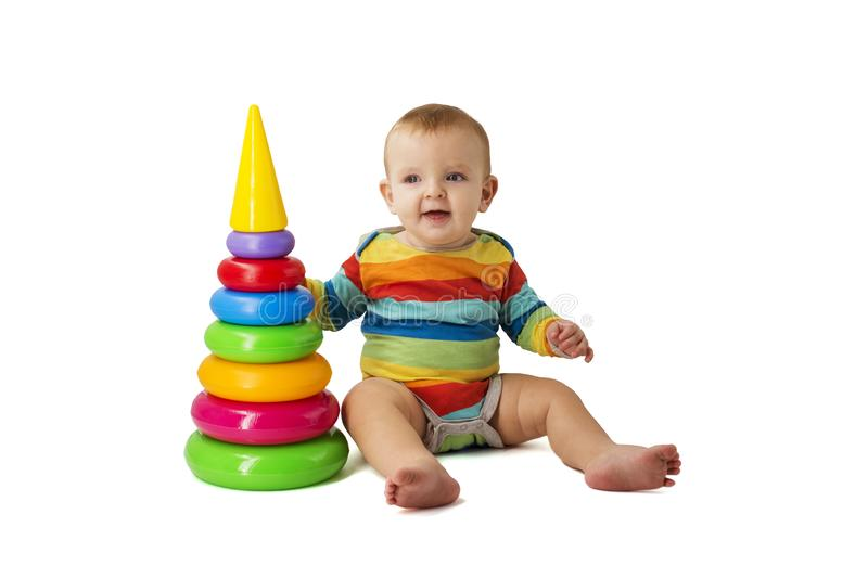Charming cute baby in overalls plays with a colored plastic pyramid sitting on a white background. A child collects a colored stock photo