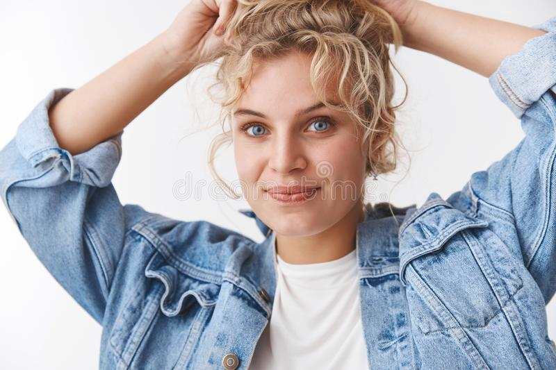 Charming cute european girlfriend curly-haired blonde fix bun hold hands head smiling friendly camera make casual daily stock photography