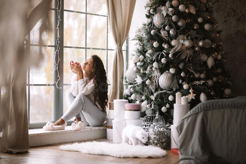 Charming dark-haired girl dressed in pants, sweater and warm slippers holds a red cup sitting on the windowsill of a. Panoramic window in the room next to the royalty free stock image