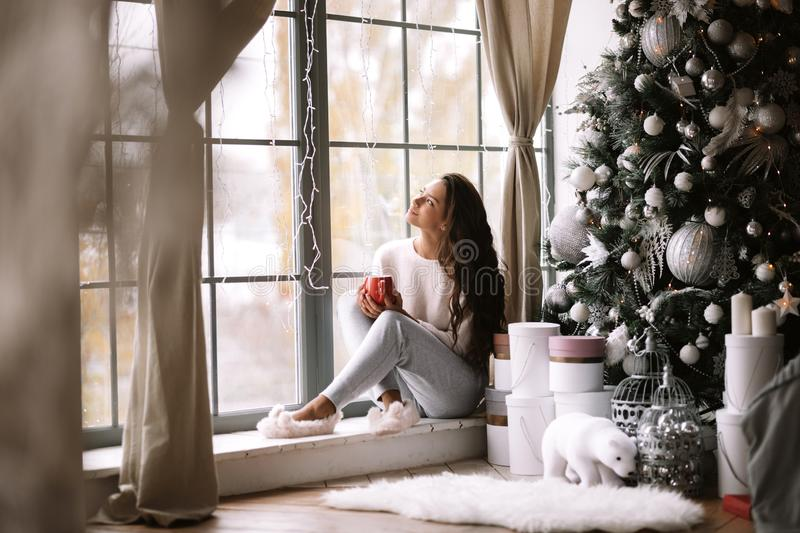 Charming dark-haired girl dressed in pants, sweater and warm slippers holds a red cup sitting on the windowsill of a. Panoramic window in the room next to the royalty free stock images