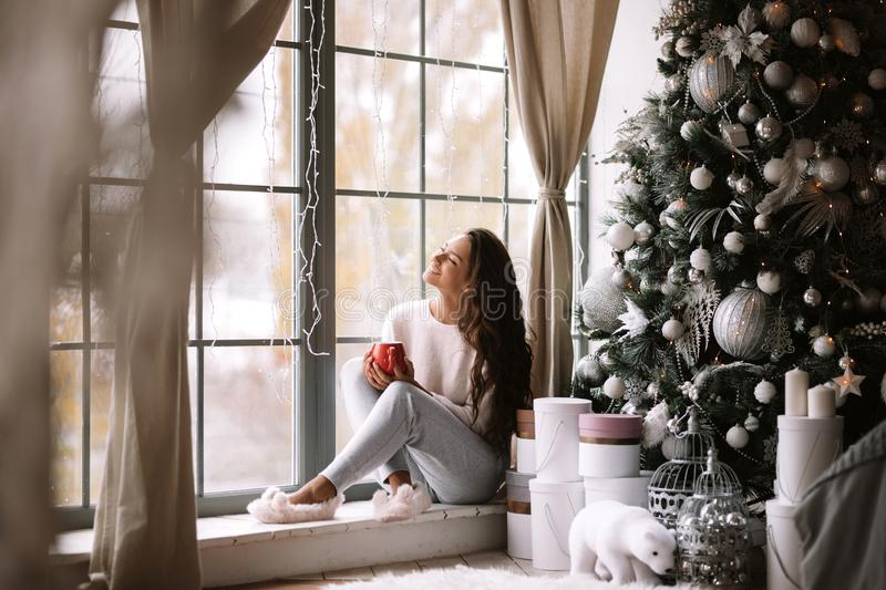 Charming dark-haired girl dressed in pants, sweater and warm slippers holds a red cup sitting on the windowsill of a. Panoramic window in the room next to the royalty free stock photo