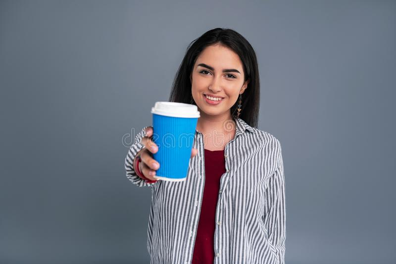 Charming dark-haired woman showing a blue coffee cup. Delicious drink. Cheerful dark-haired woman showing a blue coffee cup to the camera and smiling brightly stock images