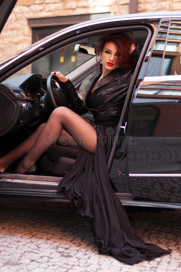 Charming driver. Red haired girl in the luxury car royalty free stock photo