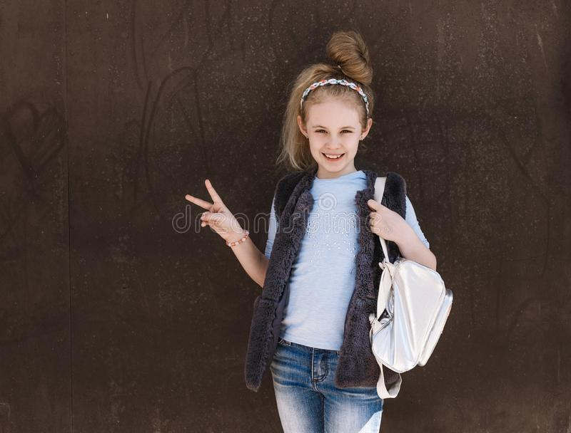 Charming eight-year-old girl in a trendy outfit with a backpack standing on the street on a sunny day royalty free stock photography
