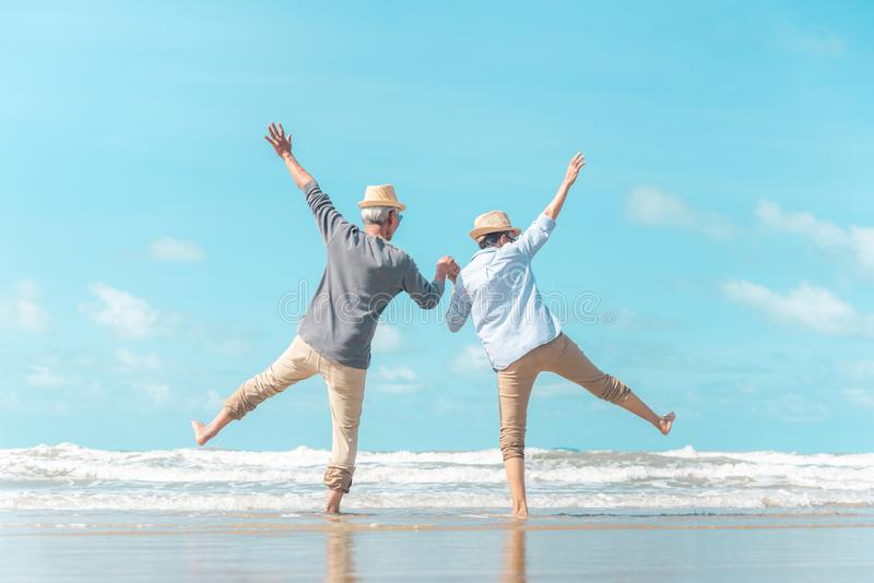 Charming elderly couple went to the beach to enjoy the sea breeze stock photos