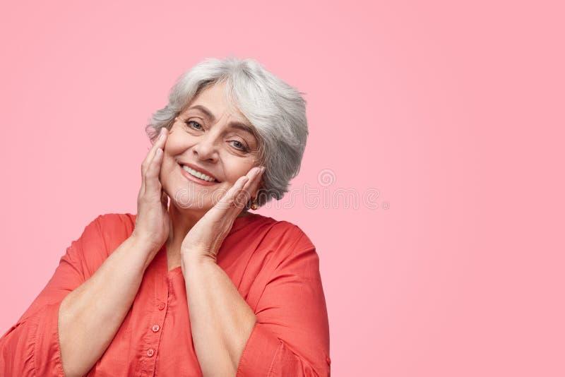 Smiling senior woman touching skin stock image