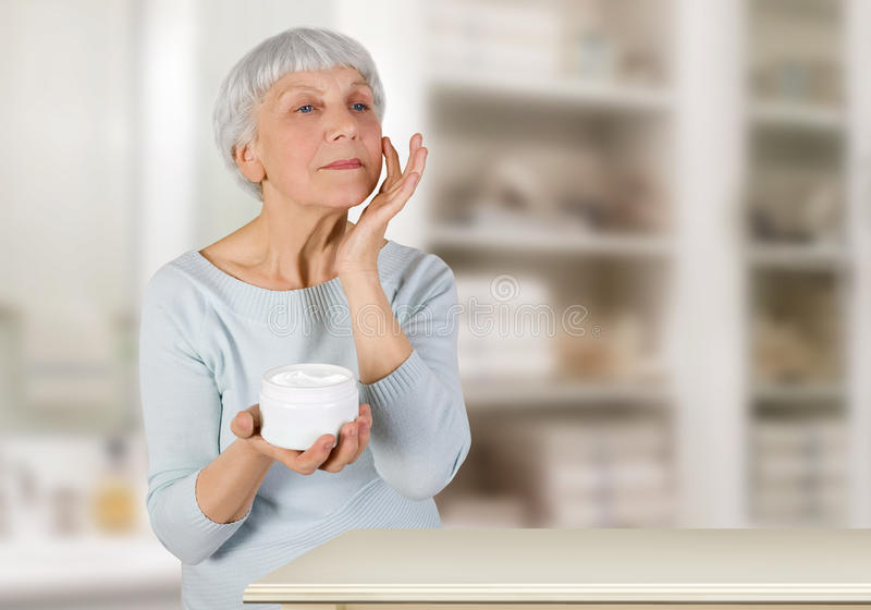 Charming elderly woman applying cosmetic cream on her face for facial skin care in bathroom at home royalty free stock photos