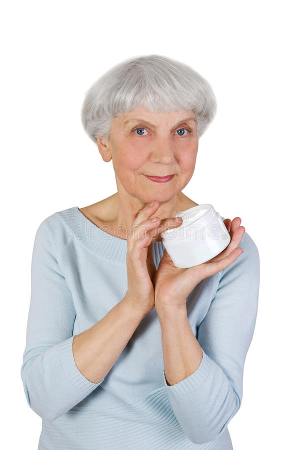 Charming elderly woman applying cosmetic cream on her face for facial skin care on a white background royalty free stock photo