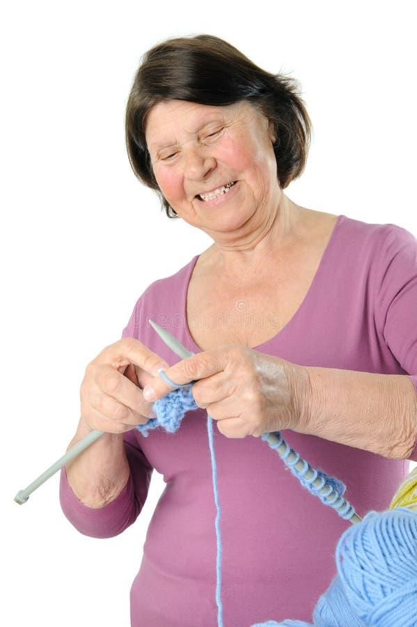 Charming elderly woman knitting large needles. royalty free stock photos