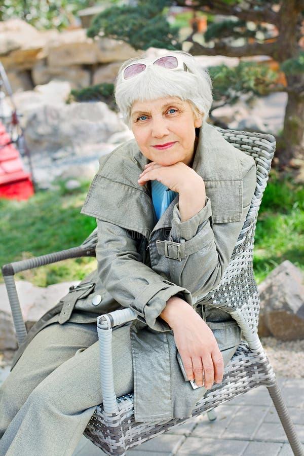 Charming elderly woman senior sitting in chair in the garden stock photo