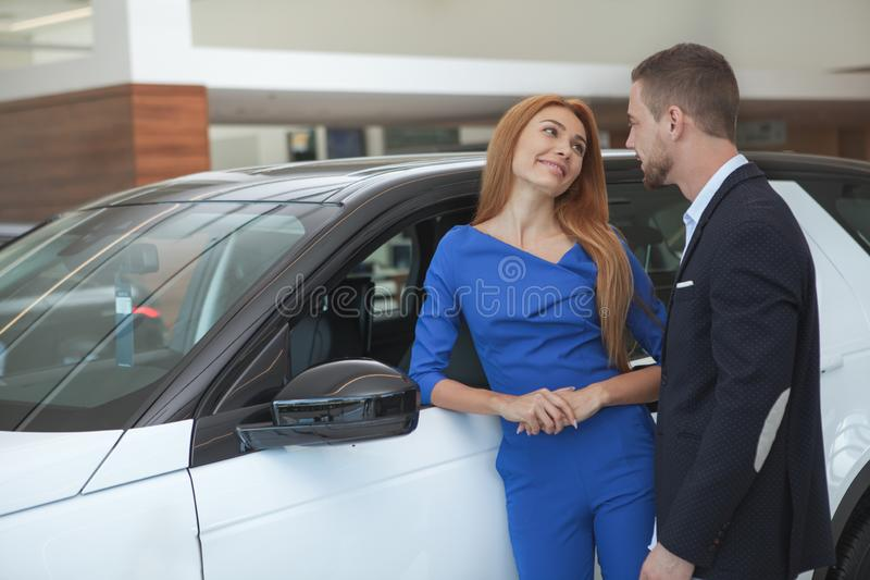 Young classy couple buying luxurious car at the dealership. Charming elegant couple chatting, choosing new automobile at dealership salon. Husband and wife royalty free stock photo
