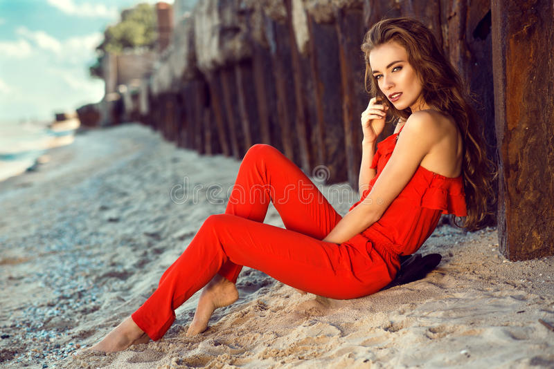 Charming elegant young woman in coral red one shoulder jumpsuit sitting on the beach at the old rusty piles stock images