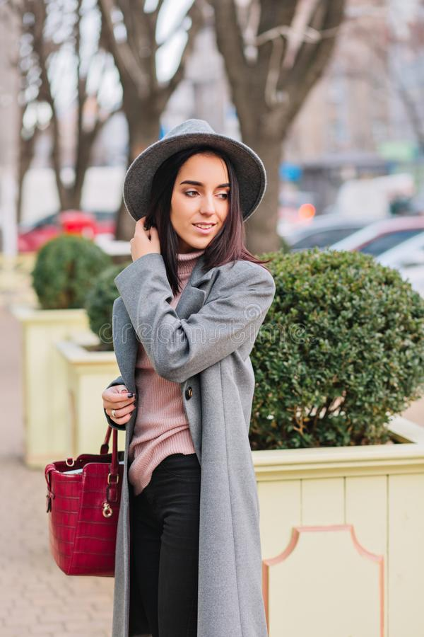 Charming elegant young woman in long grey coat, hat walking in city centre park. Luxury outlook, red bag, cheerful mood. Smiling to side, true emotions stock images