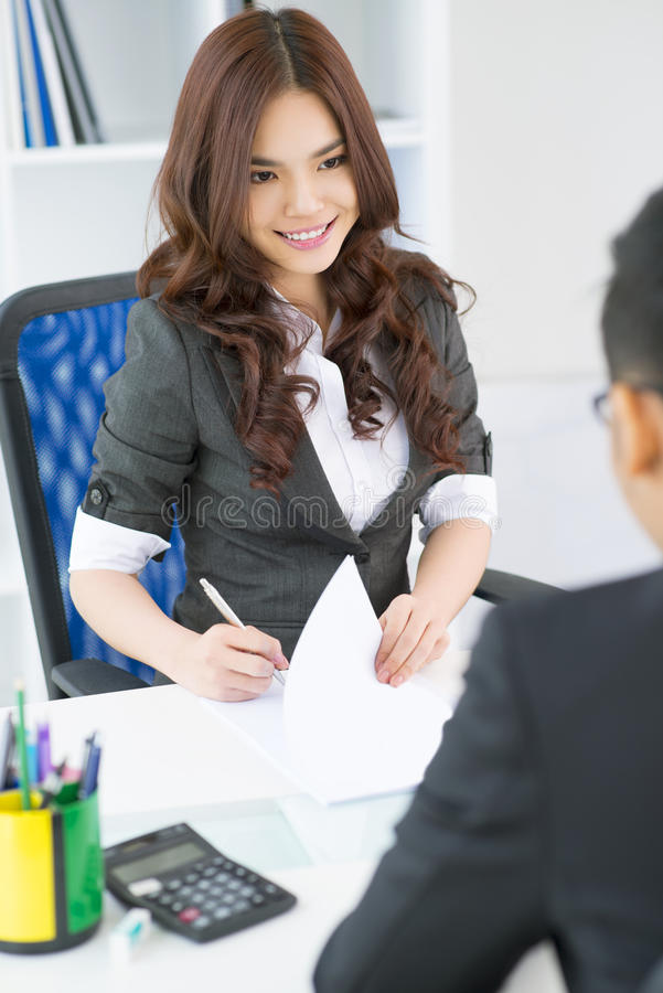 Charming employer. Vertical shot of a lovely female employer interviewing a candidate for a vacant position royalty free stock image