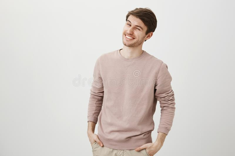 Charming european model with bristle holding hands in pockets, winking and smiling broadly at camera while standing. Against gray background. Student flirts royalty free stock image