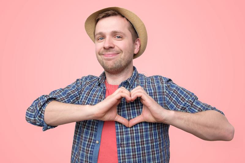 Tourist holding hands in heart gesture and smiling. Charming european tourist , holding hands in heart gesture and smiling isolated over pink background royalty free stock image