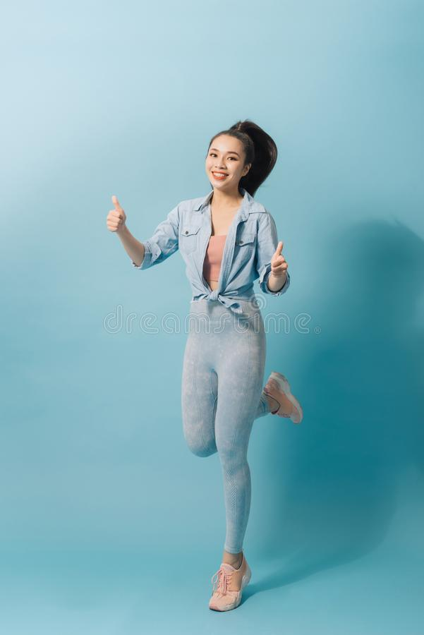Charming excited crazy woman jumping up on light blue background royalty free stock photo