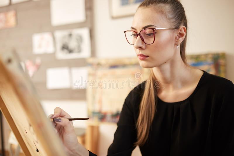 Charming fair-haired girl in glasses dressed in black blouse sits at the easel and paints a picture in the art studio.  royalty free stock photography