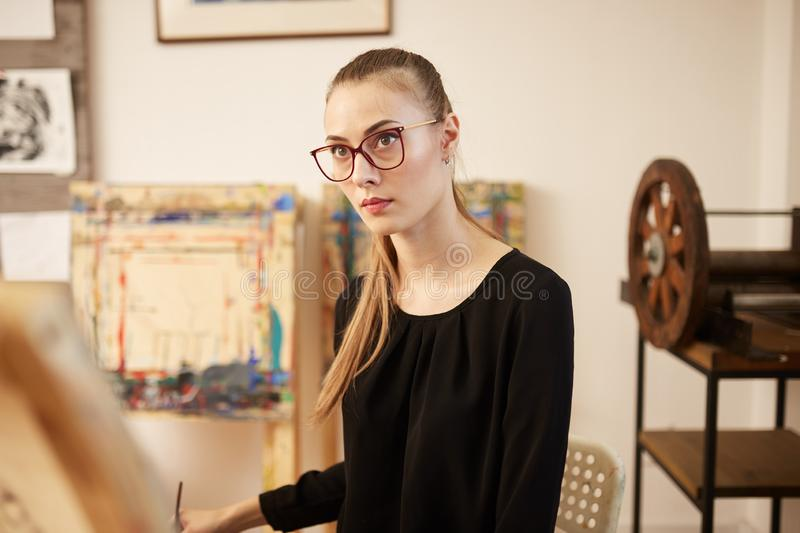 Charming fair-haired girl in glasses dressed in black blouse sits at the easel and paints a picture in the art studio.  royalty free stock images