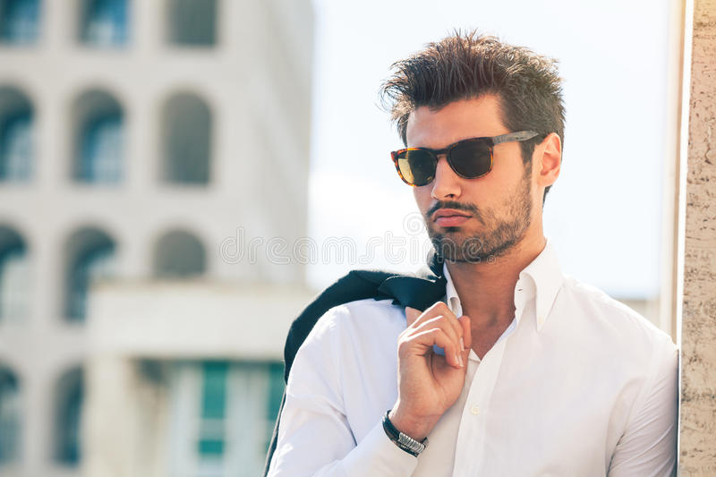 Charming and fashionable young man with sunglasses royalty free stock image
