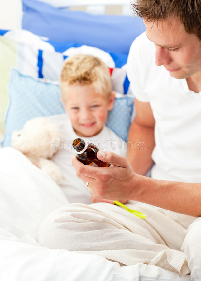 Download Charming Father Giving Cough Syrup To His Sick Son Stock Image - Image: 13077349