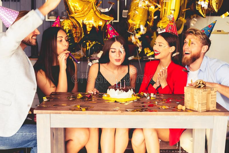 Charming female blowing on candles on birthday cake after making her wish at party. stock image