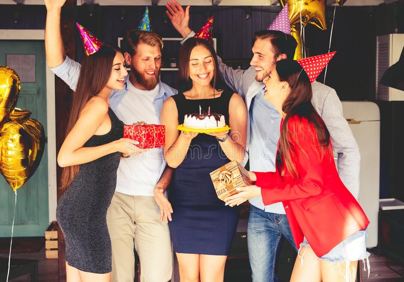 Charming female blowing on candles on birthday cake after making her wish at party. stock images
