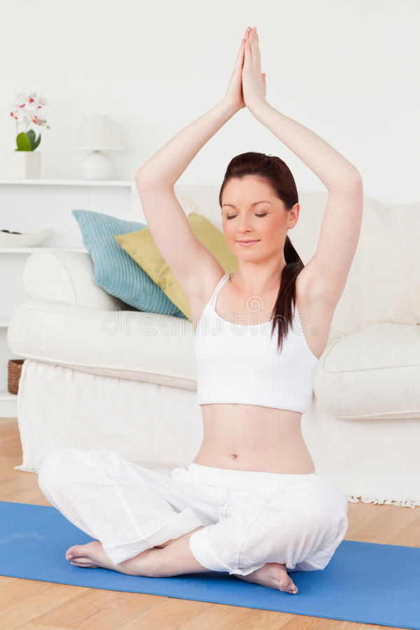 Charming female doing yoga on a gym carpet. In the living room royalty free stock images