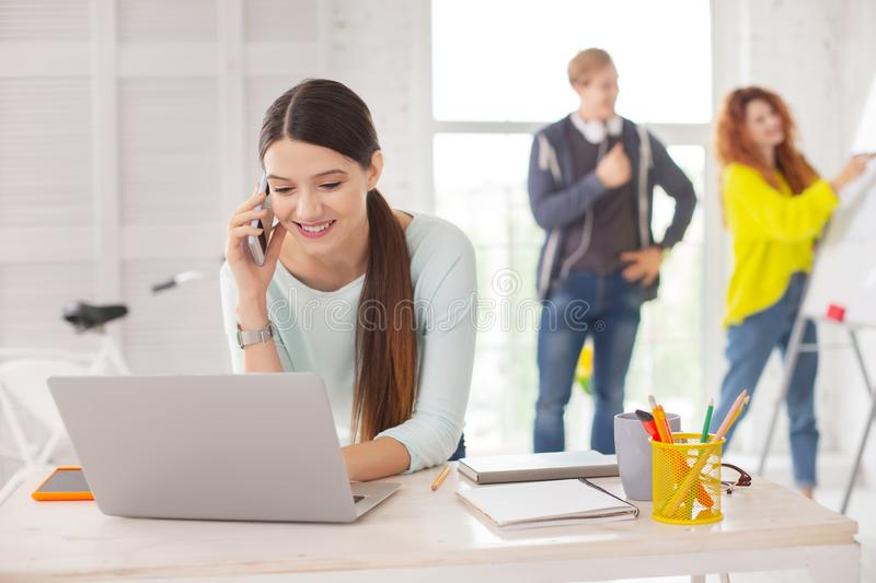 Charming female employee making call. Business call. Pleasant female employee using laptop and calling on phone stock photography