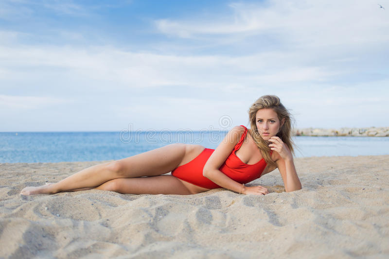 Charming female in swimwear posing outdoors. Bikini model with beautiful figure lying on the beach against blue sky background with copy space area for your text stock photos
