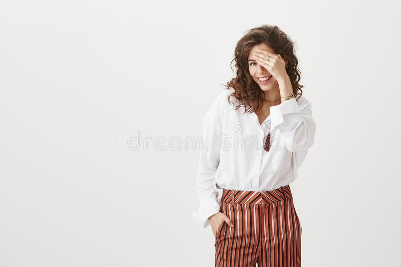 Charming feminine curly-haired female peeking aside with broad smile on face while covering one eye, being flirty and. Happy, gazing at boyfriend and beautiful stock image