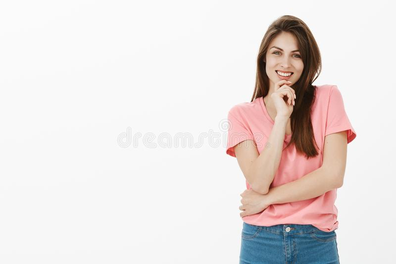 Charming feminine and flirty woman in pink stylish t-shirt, smiling broadly, holding hand on chin and gazing at camera. With interest, being charmed by cute and royalty free stock image