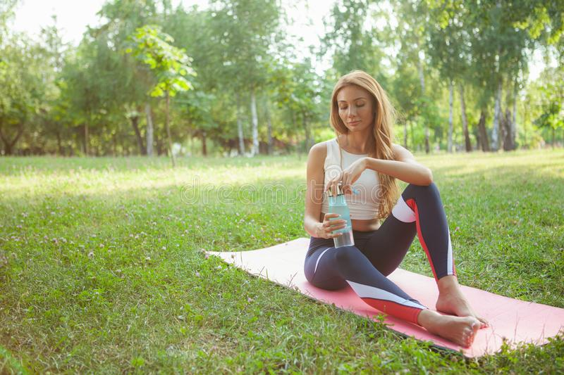Gorgeous athletic woman doing yoga at the park royalty free stock photography