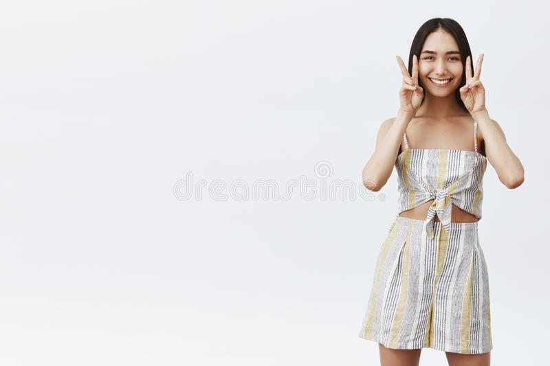 Charming friendly and stylish asian girlfriend with dark hair and cute mole under lip smiling broadly, showing peace or stock photo