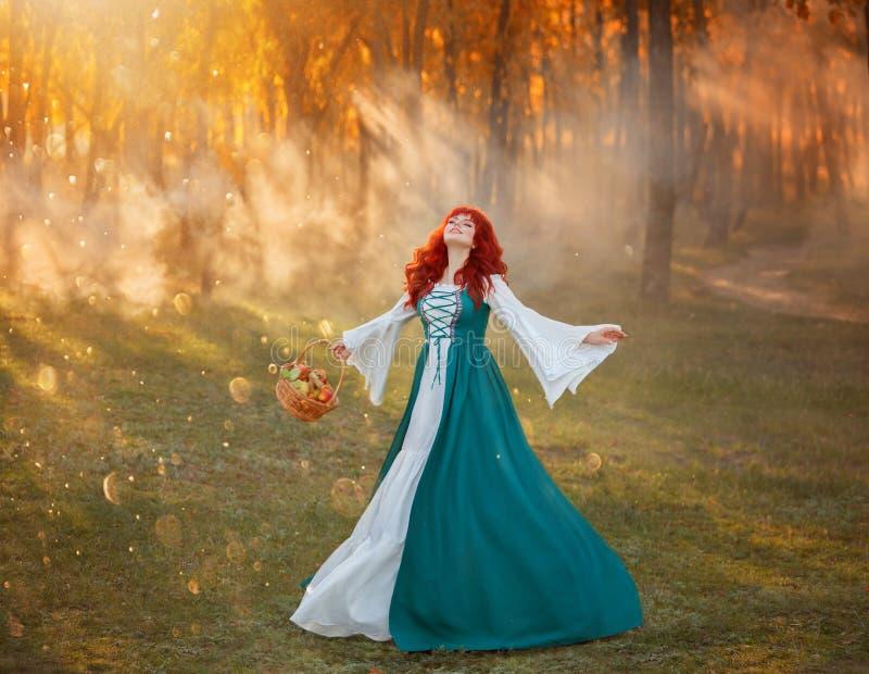 Woman in national Bavarian green costume joyfully dances on green meadow stock photo