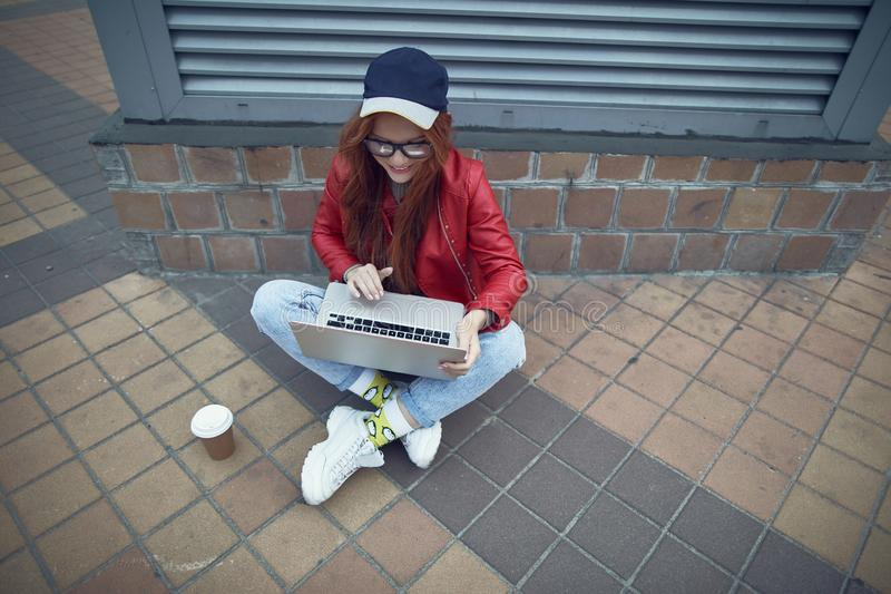 Charming girl in cap sitting with legs crossed and using laptop on the street. Top view portrait of beautiful young lady in red jacket working on notebook and stock image