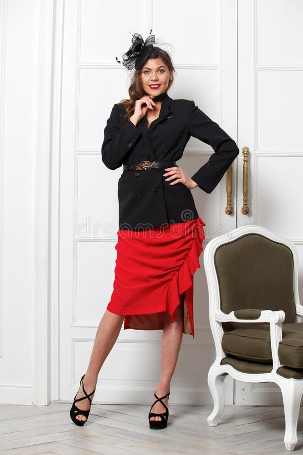 Charming girl dressed in a stylish black jacket, red skirt and a little fashionable hat poses against a white wall in royalty free stock photo