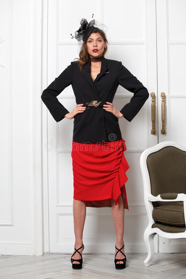 Charming girl dressed in a stylish black jacket, red skirt and a little fashionable hat poses against a white wall in royalty free stock photography