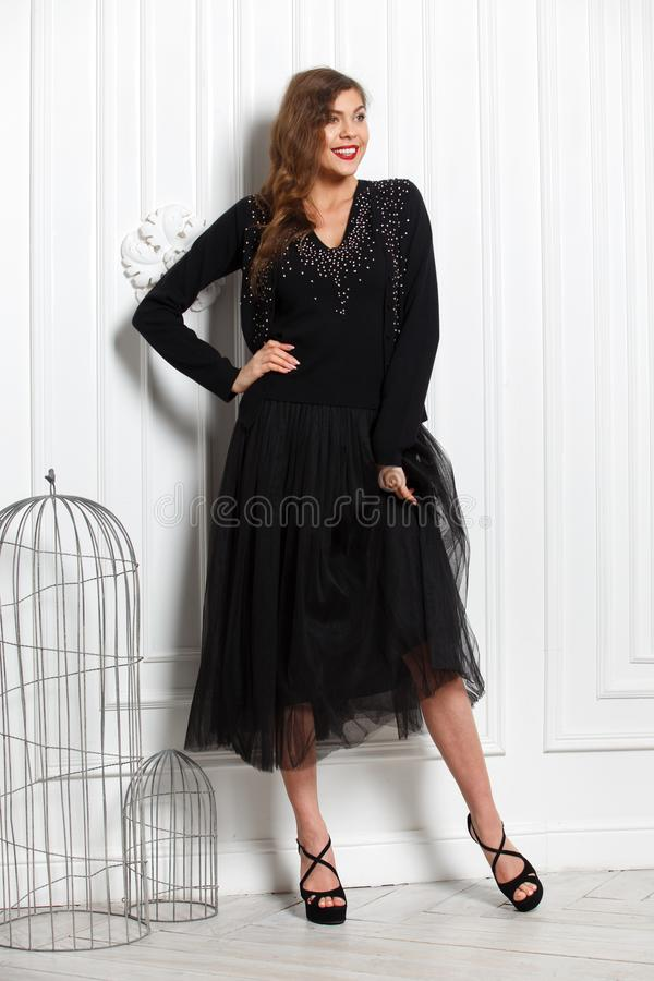 Charming girl dressed in a stylish black sweater and black full skirt poses against a white wall in the room royalty free stock image