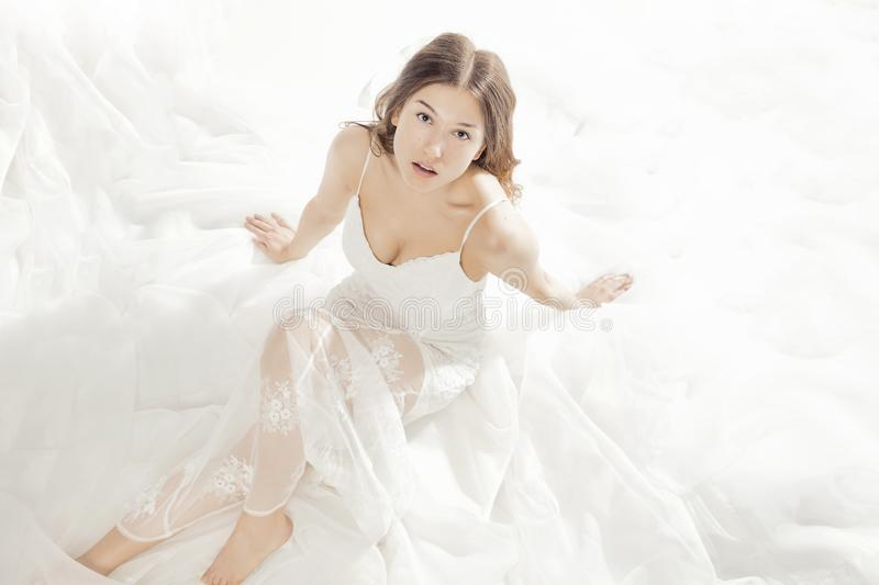 Charming girl dressed in a white dress stock photos