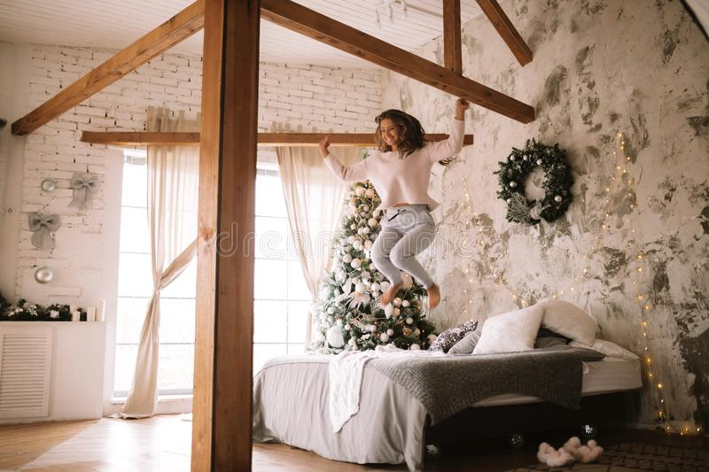 Charming girl dressed in white sweater and pants jumps on the bed with gray blanket and white pillows in a cozy. Decorated room with a New Year tree royalty free stock photos
