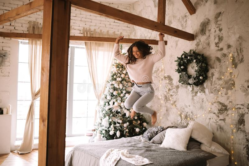 Charming girl dressed in white sweater and pants jumps on the bed with gray blanket and white pillows in a cozy. Decorated room with a New Year tree stock image