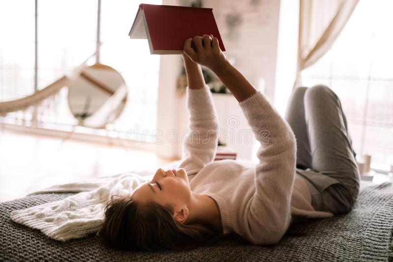 Charming girl dressed in white sweater and pants reads a book liying on the bed with gray blanket, white pillows and a. New Year gift in a cory room royalty free stock photo