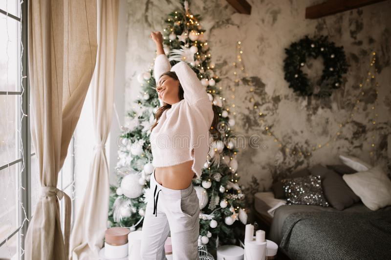 Charming girl dressed in white sweater and pants stands next to the New Year tree in front of the window and stretches. Up  in a cozy decorated room  with New stock photos